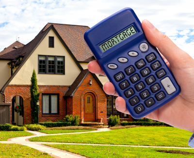 New house and hand with mortgage calculator